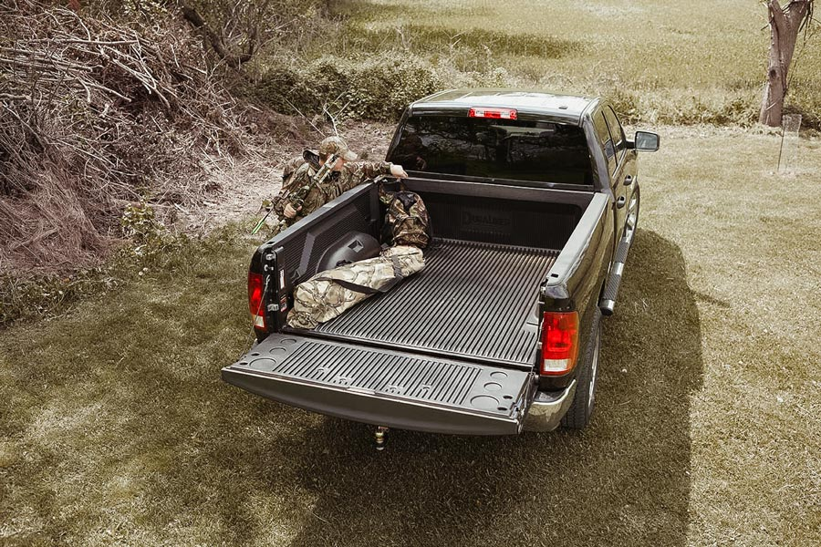 hunter placing bags in the back of a pickup truck with a duraliner in it
